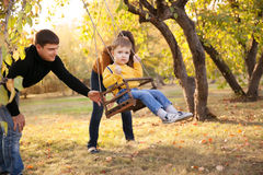 Happy family having fun on a swing ride at a garden a autumn day Stock Photography