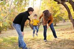 Happy family having fun on a swing ride at a garden a autumn day Stock Photos
