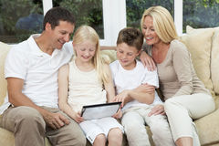 Happy Family Having Fun Tablet Computer At Home. An attractive happy, family of mother, father, son and daughter sitting on a sofa at home having fun using a Royalty Free Stock Photography