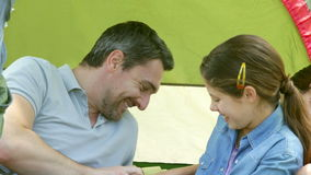 Happy family having fun in their tent on a camping trip stock video footage