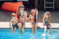 Happy family having fun time at the pool side stock photo