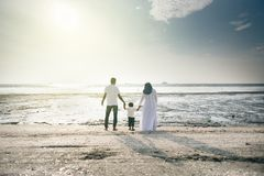 Happy family having fun time together at the beach having nice sunset view located in Pantai Remis royalty free stock photo