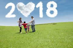 Happy family having fun together in the meadow. With clouds shaped numbers 2018 and heart in the sky stock images