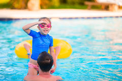 Happy family having fun together in outdoors swimming pool Stock Photography