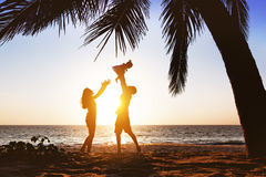 Happy family having fun under palm on sunset beach royalty free stock photos