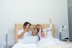 Happy family having fun while using laptop on bed Stock Image