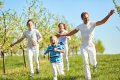 Happy family having fun walking in the garden in spring, summer. stock photography