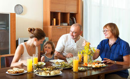 Happy family having healthy dinner with fish at home together. Happy family having healthy dinner with fish behind the table at home together stock images