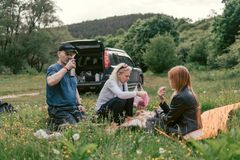 Happy family having lunch and drink tea. camping, weekend, picnic. man, woman, girl, Crossover, SUV car on backgrond stock photography