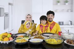 Happy family having meals together. Portrait of happy family wearing Islamic clothes while having meals together in the kitchen royalty free stock photo