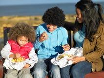 Happy family having picnic. Sitting on bench stock photos