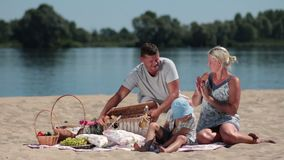 Happy family having picnic on the beach stock video footage