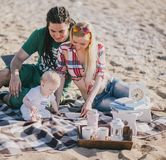 Happy family having picnic on a beach Stock Image