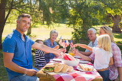 Happy family having picnic and holding american flag Royalty Free Stock Photo