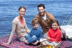 Happy family having picnic at a lake Stock Images