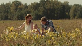 Happy family having a picnic in nature. Young mother is surprised that her son wants to eat a big piece of bread stock footage