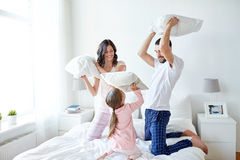 Happy family having pillow fight in bed at home. People, family and morning concept - happy child with parents having pillow fight in bed at home royalty free stock photo
