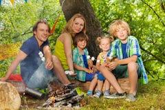 Happy family having rest and roasting marshmallow Royalty Free Stock Photos