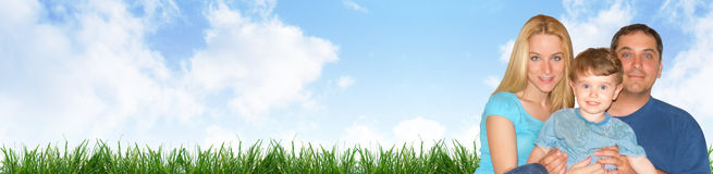 Happy Family Header with Clouds and Grass. A happy family portrait is against a nature outdoor background with clouds and grass. Use as a header and add your Royalty Free Stock Photo