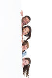 Happy family hiding behind billboard. Portrait of happy family hiding behind billboard over white background Royalty Free Stock Images