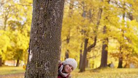 Happy family hiding behind tree at autumn park. Family, childhood, season and people concept - happy mother, father and little daughter hiding behind tree at stock video footage