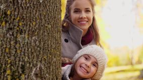 Happy family hiding behind tree at autumn park. Family, childhood, season and people concept - happy mother, father and little daughter hiding behind tree at stock footage