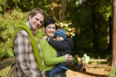 Happy family hiking. Portrait of happy family of three smiling at camera on autumn hiking stock image