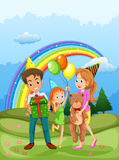 A happy family at the hilltop and a rainbow in the sky Royalty Free Stock Photography