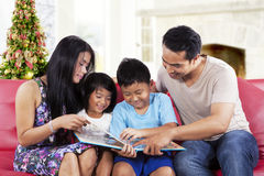 Happy family hold a story book. Portrait of happy family holding and read a story book together at home in christmas day Stock Photo