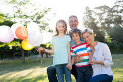Happy family holding balloons at the park Stock Photography