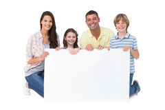 Happy family holding billboard over white background. Portrait of happy family holding billboard over white background royalty free stock photography