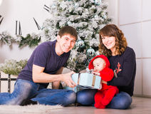 Happy family holding Christmas gifts near Xmas tree. Baby, mother and father having fun at home Stock Photography