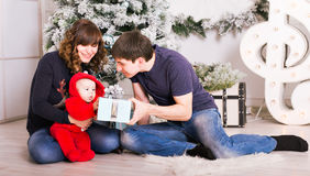 Happy family holding Christmas gifts near Xmas tree. Baby, mother and father having fun at home. Happy family holding Christmas gifts near Xmas tree. Child Stock Images