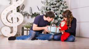 Happy family holding Christmas gifts near Xmas tree. Baby, mother and father having fun at home Royalty Free Stock Photo