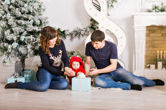 Happy family holding Christmas gifts near Xmas tree. Baby, mother and father having fun at home. Happy family holding Christmas gifts near Xmas tree. Child Royalty Free Stock Photography