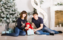 Happy family holding Christmas gifts near Xmas tree. Baby, mother and father having fun at home Stock Images