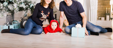 Happy family holding Christmas gifts near Xmas tree. Baby, mother and father having fun at home. Happy family holding Christmas gifts near Xmas tree. Child Royalty Free Stock Photos