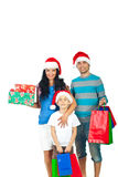 Happy family holding Christmas presents. Happy family with Santa hats holding Christmas presents isolated on white background Stock Images
