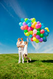 Happy family holding colorful balloons. Mom, ded and two daughte Stock Photos