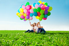 Happy family holding colorful balloons. Mom, ded and two daughte Stock Photography
