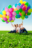 Happy family holding colorful balloons. Mom, ded and two daughte Stock Image