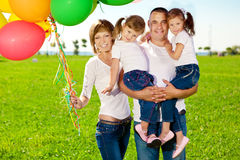 Happy family holding colorful balloons. Mom, ded and two daughte Royalty Free Stock Photos