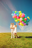 Happy family holding colorful balloons. Mom, ded and two daughte Royalty Free Stock Image