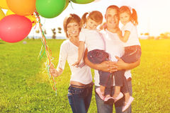 Happy family holding colorful balloons. Mom, ded and two daughte Stock Photo