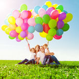 Happy family holding colorful balloons. Mom, ded and two daughte Stock Images
