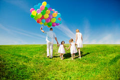 Happy family holding colorful balloons outdoor. Mom, ded and two Stock Photos