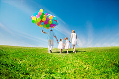 Happy family holding colorful balloons outdoor. Mom, ded and two Royalty Free Stock Photo