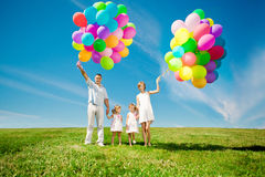 Happy family holding colorful balloons outdoor. Mom, ded and two Royalty Free Stock Photos