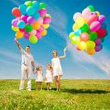 Happy family holding colorful balloons outdoor. Mom, ded and two Royalty Free Stock Image