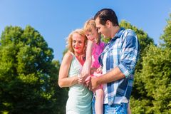 Happy family holding each other cheek to cheek. Mother, father, child, holding each other close and cuddling Stock Image